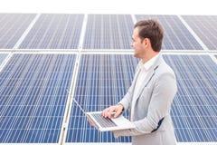 Un hombre sostiene un ordenador portátil en sus manos y mira en la distancia, colocándose al lado de los paneles solares outdoors Fotos de archivo libres de regalías