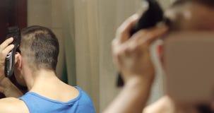 Un hombre sostiene un pequeño espejo en sus manos y afeita el pelo en su cabeza almacen de metraje de vídeo