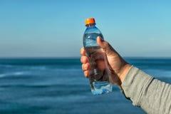Un hombre sostiene una botella plástica de agua potable en su mano, colocándose en el océano foto de archivo