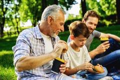 Un hombre, su padre mayor y el hijo se están sentando en un parque en una comida campestre Un muchacho se está sentando con un sm Imagen de archivo