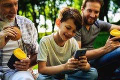 Un hombre, su padre mayor y el hijo se están sentando en un parque en una comida campestre Un muchacho se está sentando con un sm Fotografía de archivo