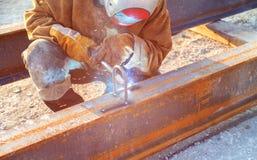 Un hombre suelda con autógena un producto de metal a una soldadora imagen de archivo