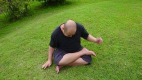 Un hombre tailandés asiático gordo de la cabeza calva está enojado como un niño de los escombros y después la palpitación wriggli metrajes