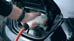 Un hombre tapa un cable de carga a su coche eléctrico Carga eléctrica innovadora del coche híbrido almacen de video