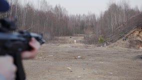 Un hombre tira en una blanco con un rifle de asalto en la radio de tiro metrajes