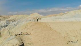 Un hombre tira una foto que se coloca encima de una colina entre las monta?as del desierto