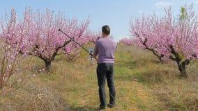 Un hombre tira un vídeo en un jardín floreciente almacen de metraje de vídeo