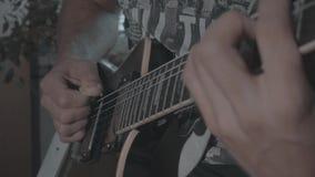 Un hombre toca una guitarra eléctrica negra almacen de metraje de vídeo