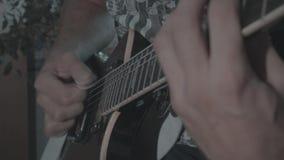 Un hombre toca una guitarra eléctrica negra metrajes