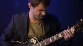 Un hombre toca una guitarra eléctrica y canta en un cuarto oscuro almacen de metraje de vídeo