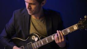 Un hombre toca una guitarra eléctrica y canta en un cuarto oscuro metrajes