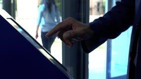 Un hombre toma un boleto a la cola en la clínica Mano del hombre en el traje usando cierre terminal para arriba El tacto del homb almacen de metraje de vídeo