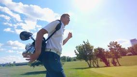 Un hombre toma un bolso con los clubs y los paseos en un campo de golf almacen de video