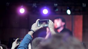 Un hombre toma un concierto de la banda de rock en su smartphone almacen de video