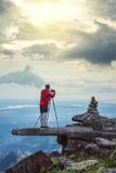 Un hombre toma una foto en un top de la roca de la montaña en Tailandia Fotografía de archivo