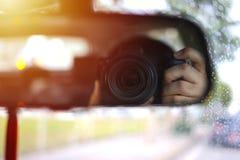 Un hombre tomaba una imagen de sí mismo a través del retrovisor fotografía de archivo libre de regalías