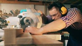 Un hombre trabaja con el banco de la sierra mientras que corta la madera en un taller almacen de video