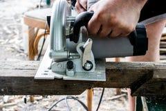 Un hombre trabaja con sus manos y una herramienta de la construcción Eléctrico vio Trabajo sobre los tableros de madera Para cort fotografía de archivo