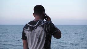 Un hombre trabaja en horas extras en el teléfono al fin de semana en un fondo hermoso del paisaje metrajes