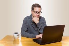 Un hombre trabaja en un ordenador portátil mientras que se sienta Fotografía de archivo