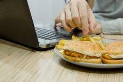Un hombre trabaja en un ordenador y come los alimentos de preparación rápida imagen de archivo