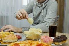 Un hombre trabaja en un ordenador y come los alimentos de preparación rápida fotos de archivo