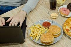 Un hombre trabaja en un ordenador y come los alimentos de preparación rápida comida malsana: BU imagen de archivo