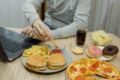 Un hombre trabaja en un ordenador y come los alimentos de preparación rápida comida malsana: BU fotografía de archivo libre de regalías