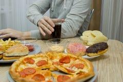 Un hombre trabaja en un ordenador y come los alimentos de preparación rápida comida malsana: BU fotos de archivo libres de regalías