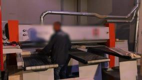 Un hombre trabaja para la máquina en una fábrica de los muebles, interior industrial metrajes