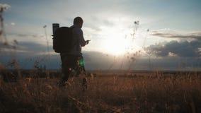 Un hombre tur?stico joven con una mochila utiliza un tel?fono m?vil En los rayos del sol poniente concepto del recorrido Siempre  almacen de video