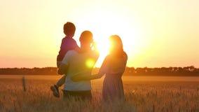 Un hombre, una mujer y un soporte del niño en un campo de trigo y señalar sus fingeres en la puesta del sol El padre detiene a su metrajes