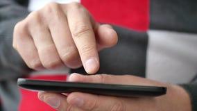 Un hombre usando los apps en un smartphone móvil de la pantalla táctil