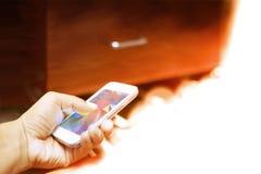 Un hombre utiliza el smartphone en lámpara anaranjada imagen de archivo libre de regalías