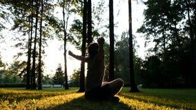 Un hombre utiliza el teléfono y aumenta sus manos para arriba en la puesta del sol que se sienta en la hierba en el parque almacen de video