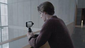 Un hombre utiliza un estabilizador del cardán para tirar en un dispositivo móvil la tecnología del futuro en una foto y un vídeo  almacen de video