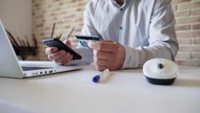 Un hombre utiliza un smartphone para las compras en línea, incorpora la información de la tarjeta de crédito almacen de metraje de vídeo