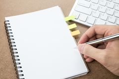 Un hombre va a escribir algo en la página en blanco del cuaderno fotografía de archivo libre de regalías