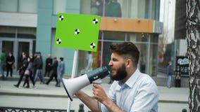 Un hombre va a una reunión con un megáfono en sus manos en primer de la cámara lenta