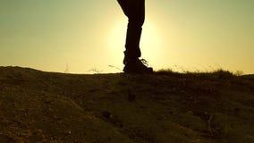 Un hombre-viajero valeroso, subiendo al top de una montaña, caminando a lo largo de una trayectoria a lo largo de un canto rocoso almacen de video