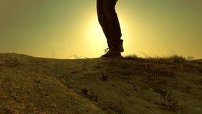 Un hombre-viajero valeroso, subiendo al top de una montaña, caminando a lo largo de una trayectoria a lo largo de un canto rocoso almacen de metraje de vídeo