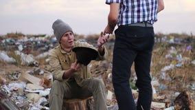 Un hombre viene a un hombre sin hogar y le da el dinero almacen de metraje de vídeo