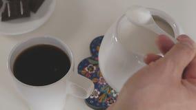 Un hombre vierte una cucharadita de azúcar del cuenco de azúcar en una taza de café almacen de video