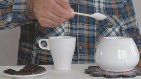 Un hombre vierte una cucharadita de azúcar del cuenco de azúcar en una taza de café metrajes