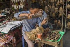 Un hombre vietnamita en la ciudad antigua de Hoian que talla de los juguetes y de los recuerdos hechos a mano de madera en taller Imagen de archivo libre de regalías