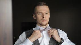 Un hombre viste y endereza una corbata de lazo almacen de metraje de vídeo