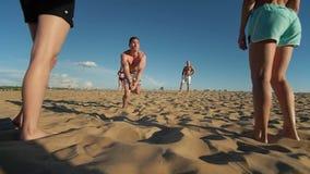 Un hombre vuela para arriba en el aire, hace la transferencia de la bola mientras que juega a voleibol de playa y se cae en la ar almacen de metraje de vídeo