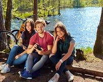 Un hombre y dos muchachas que usan una cámara digital compacta en el r salvaje Foto de archivo