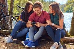 Un hombre y dos muchachas que usan una cámara digital compacta en el r salvaje Foto de archivo libre de regalías