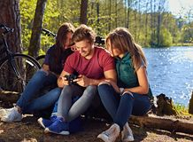 Un hombre y dos muchachas que usan una cámara digital compacta en el r salvaje Fotografía de archivo libre de regalías